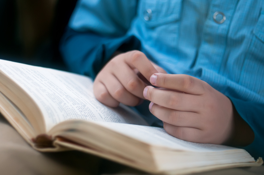 Child's hands are on the open book